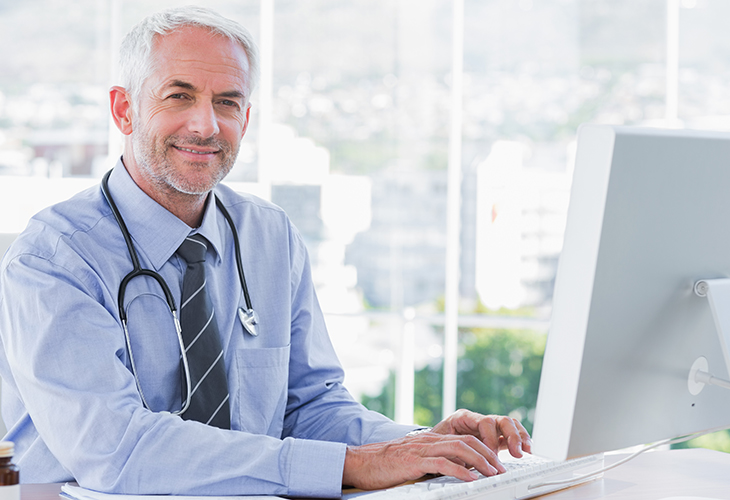 Smiling male doctor with stethoscope sitting at a computer