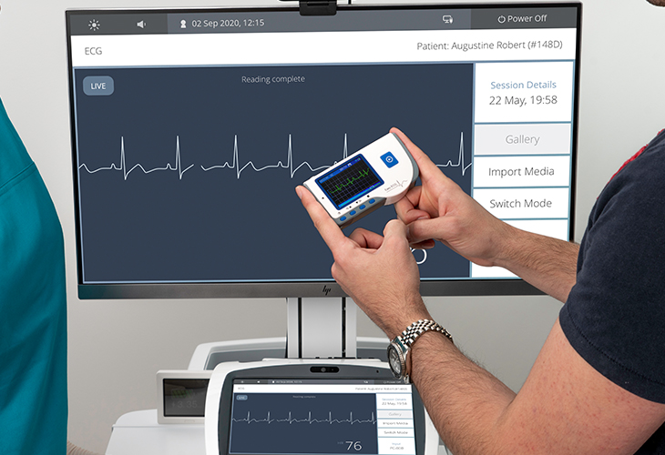 Patient using portable ECG machine with Visionflex ProEX Desktop telehealth device showing ECG heart rate trace line on screen