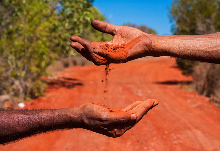 Red dirt passing through one hand to another